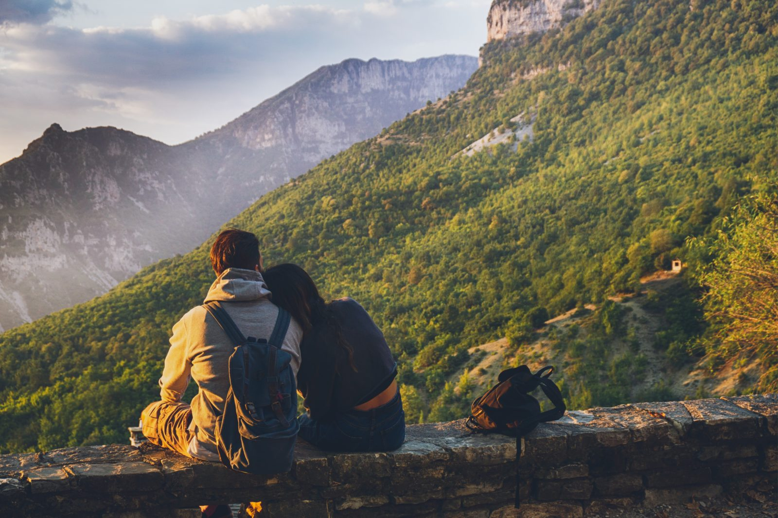 Couple sitting with backpacks looking over valley